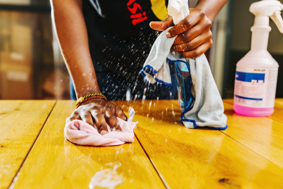 vrouw poetst houten tafel met spray