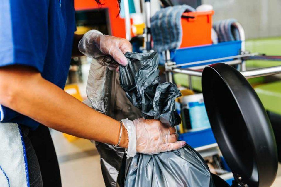 vrouw stopt vuilniszak in vuilnisbak
