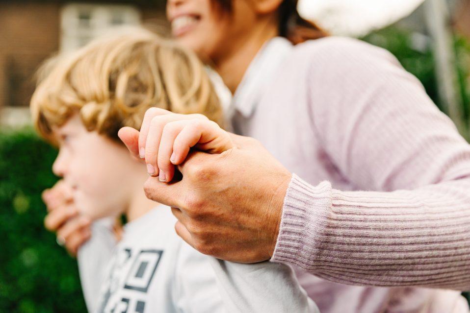 vrouw houd handen van jongetje vast