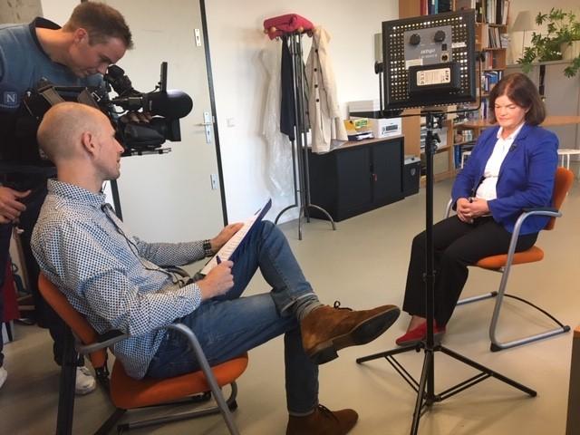 vrouw wordt geinterviewed door journalist en camera