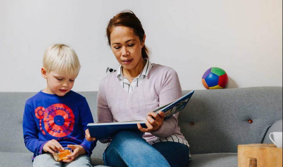 vrouw leest voor voor jongen op bank