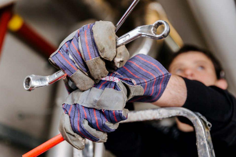 man met handschoenen houd gereedschap vast