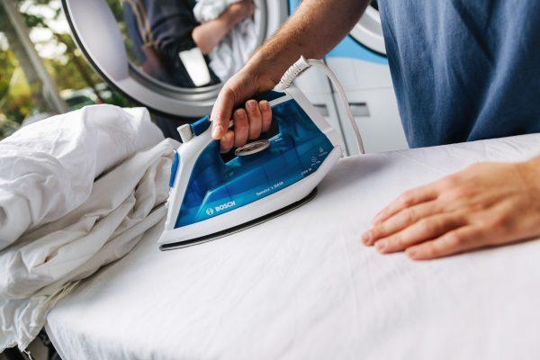 handen houden blauw strijkijzer vast