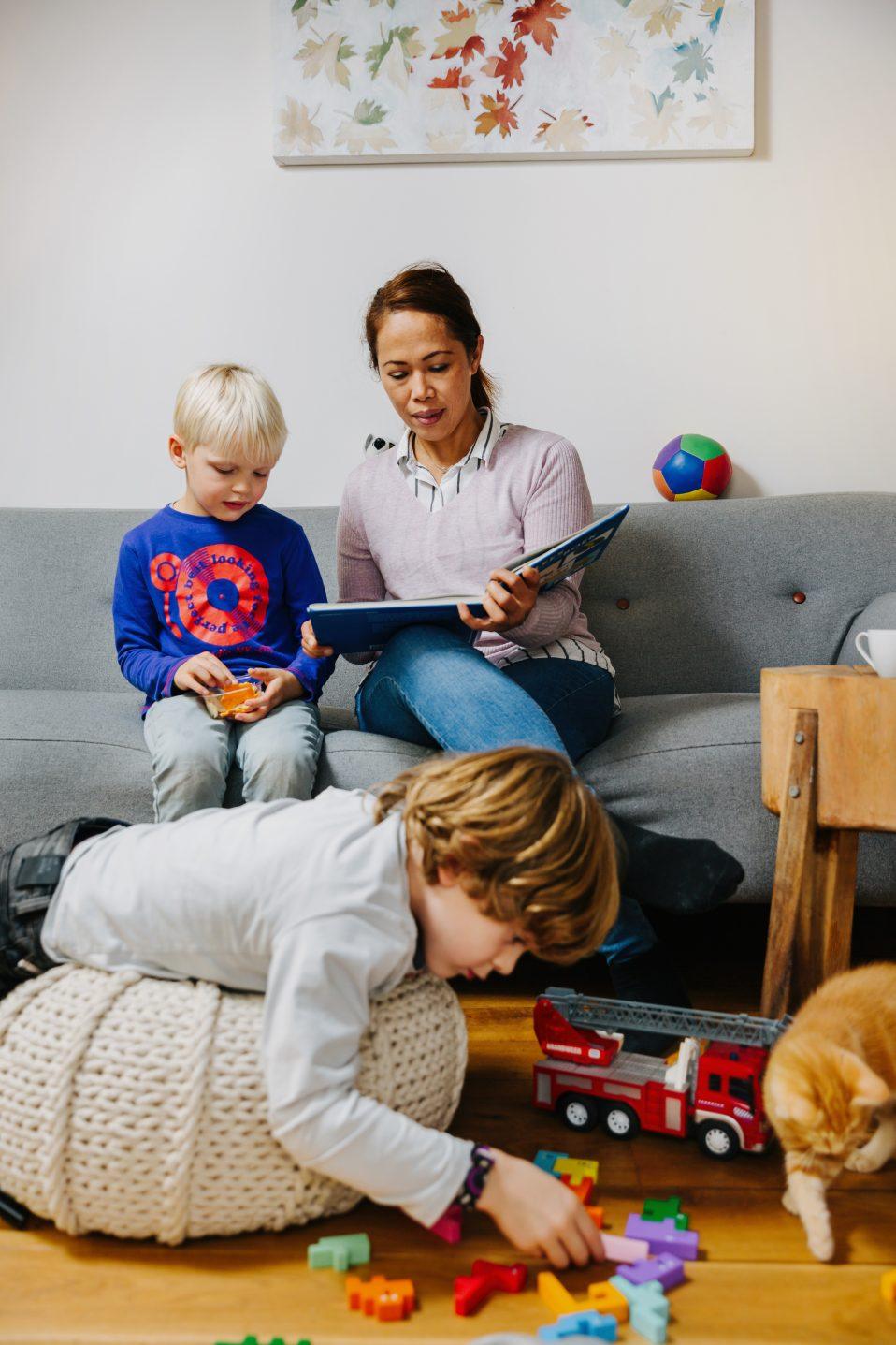 vrouw leest voor aan kind en jongen speelt op de grond
