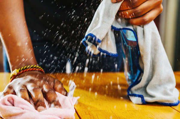 handen houden schoonmaakspray en schoonmaakdoekje vast